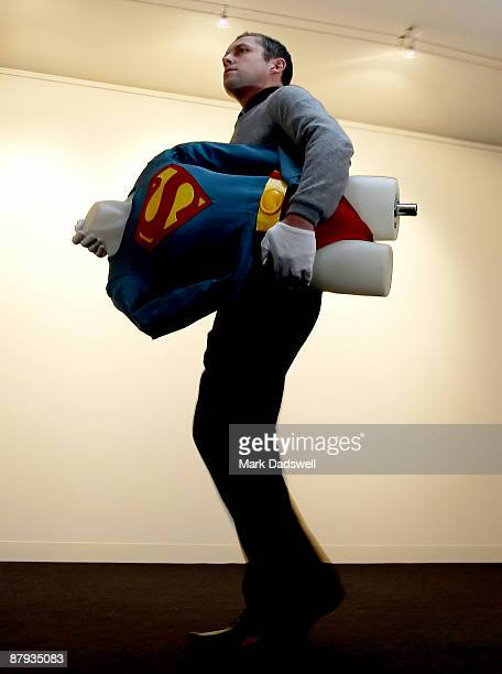 Giles Moon Head of Collectables at Bonhams and Goodman carries the Superman costume as worn by Christopher Reeve in Superman III at the Auction House...