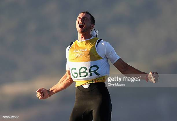 Giles Scott of Great Britain celebrates clinching a gold medal after his second Finn Class race on Day 9 of the Rio 2016 Olympic Games at the Marina...