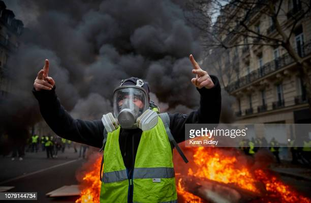 """Gilet Jaune in front of a barricade which is on fire near the Champs Elysees on December 8, 2018 in Paris, France. The """"Yellow Vest"""" protests have..."""