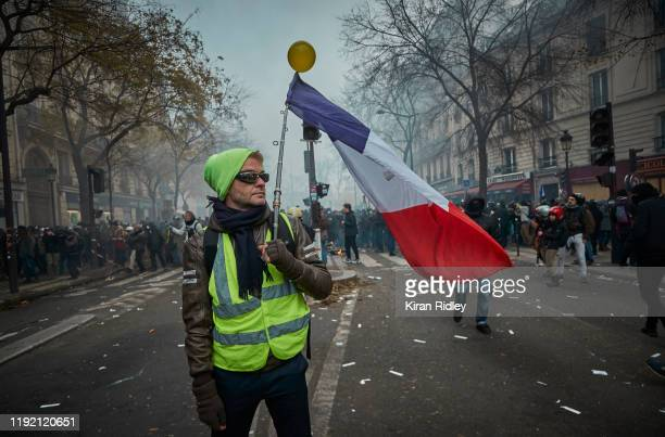 Gilet Jaune or Yellow Vest' holds a French Tricolor amidst tear gas as protestors and French Riot Police clash during a rally near Place de...