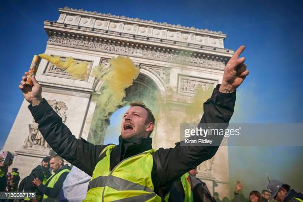 Gilet Jaune or 'Yellow Vest' protestor chants holding a yellow flare aloft during Act 14 of demonstrations at the Arc de Triomphe on February 16 2019...