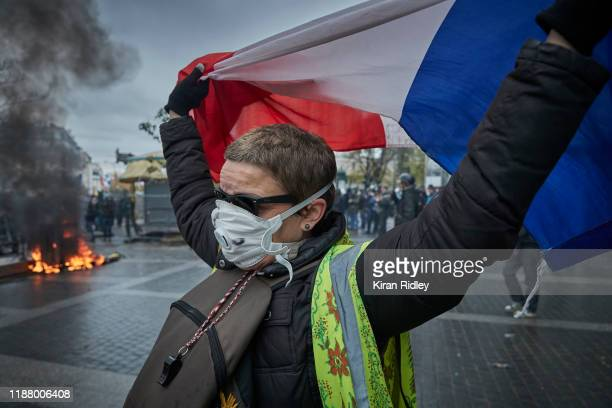 Gilet Jaune, or Yellow Vest, protestor holds a French Tricolor as protests to mark the Anniversary of the Gilets Jaune movement turn violent at Place...