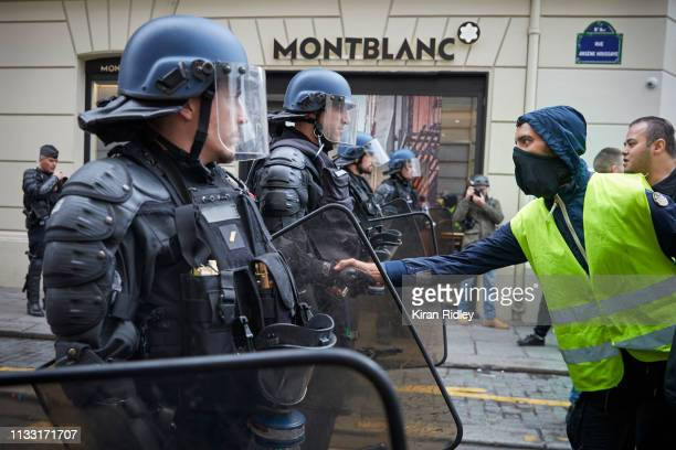 Gilet Jaune or 'Yellow Vest' protestor shakes hands with a French Riot Policeman during Act 16 of demonstrations near the Champs Elysees in an act...