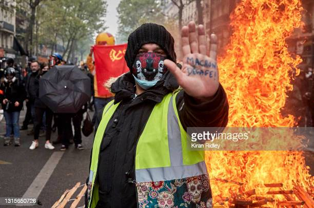 Gilet Jaune, or yellow vest, protestor stands in front of a burning barricade holding his hand up with an inscription calling for President Macron to...
