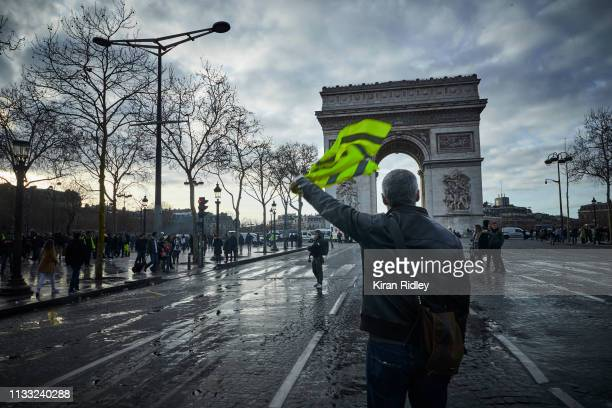 Gilet Jaune or 'Yellow Vest' protestor waves his yellow vest in the air during Act 16 of demonstrations near the Arc de Triomphe on March 02 2019 in...