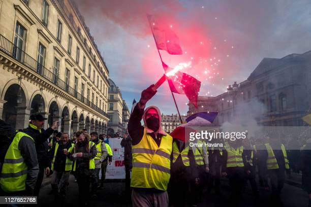 Gilet Jaune protester holds a flare while marching during the general strike march on February 05 2019 in Paris France Some 14000 people demonstrated...