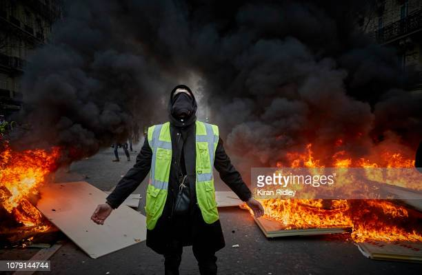 """Gilet Jaune runs through a barricade which is on fire near the Champs Elysees on December 8, 2018 in Paris, France. The """"Yellow Vest"""" protests have..."""