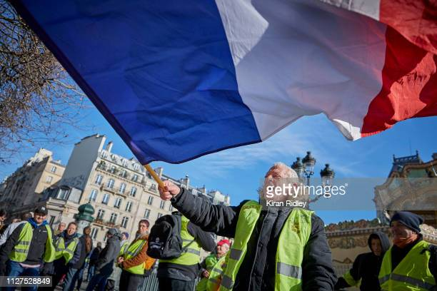 Gilets Jaune or yellow vests protestor flies the French tricolor flag as part of the National General Strike, called for by the CGT Union, in front...