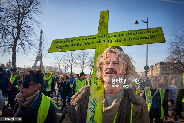 Gilets Jaunes or 'Yellow Vest' protestor holding a crucifix and wearing a scull cap to show solidarity with the Jewish community during a second...