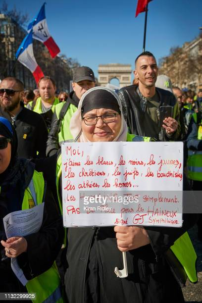 Gilets Jaunes or 'Yellow Vest' protestor holds a sign saying 'I Love Whites Blacks Yellows Christians Jews Buddhists atheists gays simply all humans...