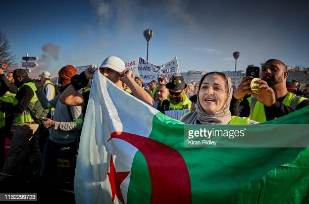 Gilets Jaunes or 'Yellow Vest' protestor waves an Algerian Flag during the fifteenth Saturday of protests on February 23, 2019 in Paris, France....