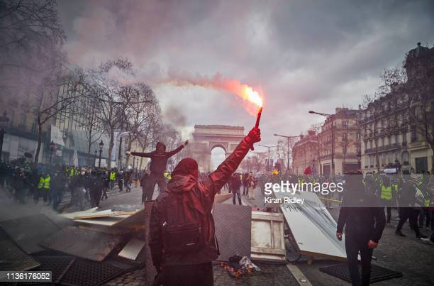 """Gilets Jaunes or 'Yellow Vest' protestors celebrate around a barricade on the Champs Elysees as Act 18 of protests, presented as an """"ultimatum"""" to..."""