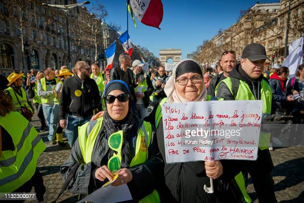 Gilets Jaunes or 'Yellow Vest' protestors hold a sign saying 'I Love Whites Blacks Yellows Christians Jews Buddhists atheists gays simply all humans...