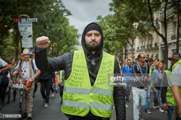 Gilets Jaunes protestors chant and sing against President Macron as they march through Paris during Act 37 of demonstrations on July 27, 2019 in...