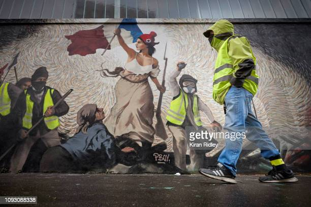 Gilets Jaunes walks past the 9 metre mural by street artist Pascal Boyart, a homage to the 'Gilets Jaunes' or 'Yellow Vest' movement, presenting a...