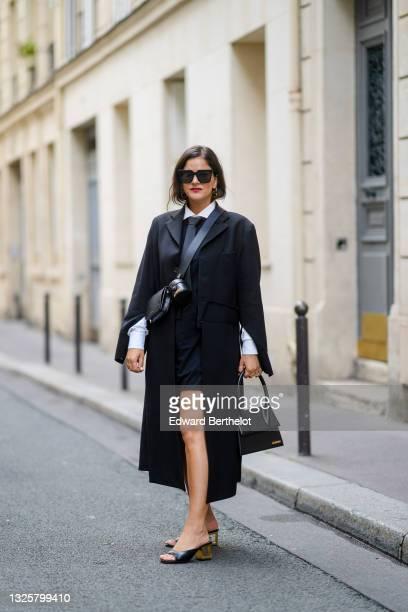 Gili Biegun @joysworld_ wears a white shirt, a tie, a black long coat, a crossbody Jacquemus bag, a black leather Jacquemus handbag, a short dress,...