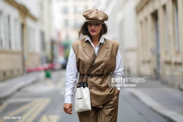 Gili Biegun @joysworld_ wears brown / khaki leather beret hat, a sleeveless double breasted brown / beige / khaki blazer jacket, a white shirt, a...