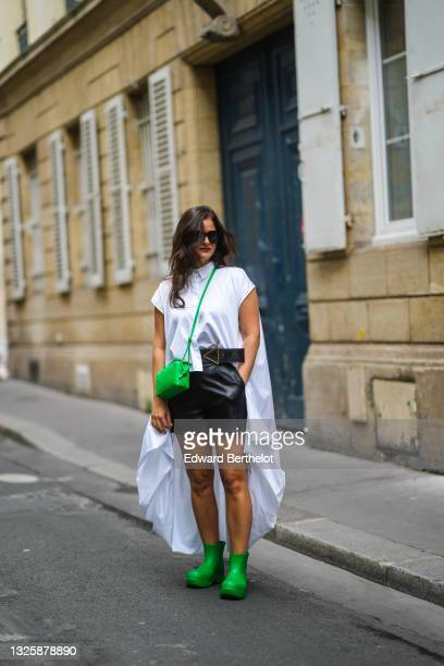 Gili Biegun @joysworld_ wears sunglasses, a white long shirt with integrated cape from Celine, a large belt, a neon green woven leather Bottega...