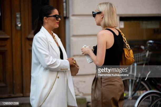 Gili Biegun wearing white suit and carrying beige Bottega Veneta bag and little Jacquemus shoulder bag and Justina Czerniak wearing brown leather...