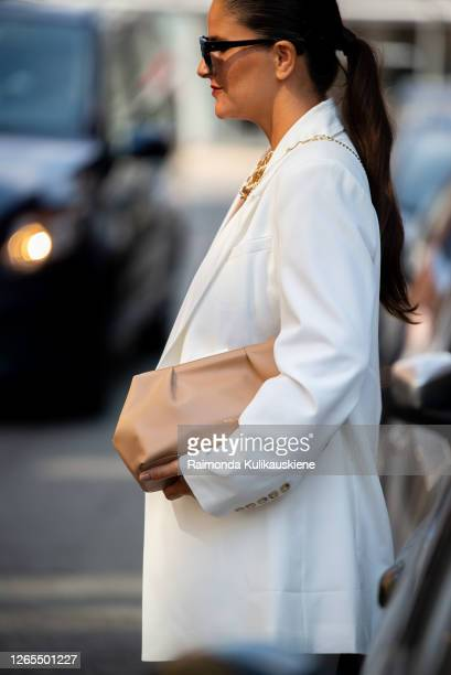 Gili Biegun wearing white suit and carrying beige Bottega Veneta bag and little Jacquemus shoulder bag outside Malaikaraiss during Copenhagen fashion...