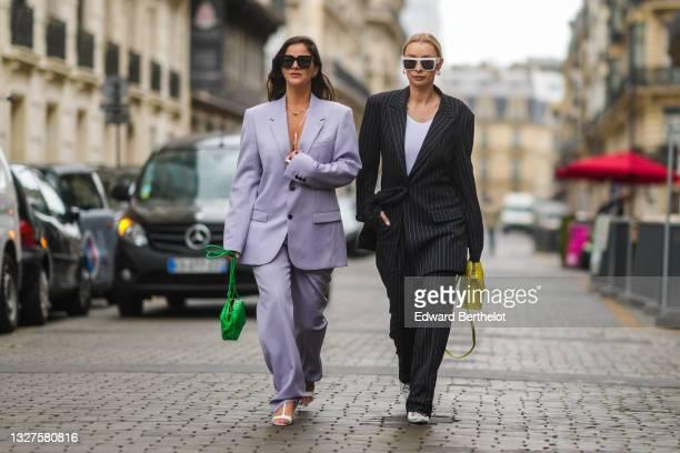 Gili Biegun wears black sunglasses, silver earrings, silver chain pendant necklace, a pale purple long oversized with shoulder pads blazer jacket,...