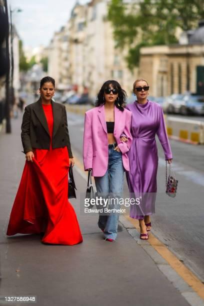 Gili Biegun wears gold Fendi earrings, gold earrings, a red long flowing dress, gray short blazer jacket, a black shiny leather Chiquito handbag from...