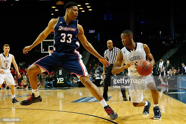 G Gill of the Duquesne Dukes defends against Nick Griffin of the George Washington Colonials during the Second Round of the Atlantic 10 Basketball...