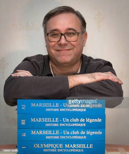 Gilles Castagno poses at his home with his encyclopedia of four volume of the Olympic of Marseille on December 4 in Marseille southern France...