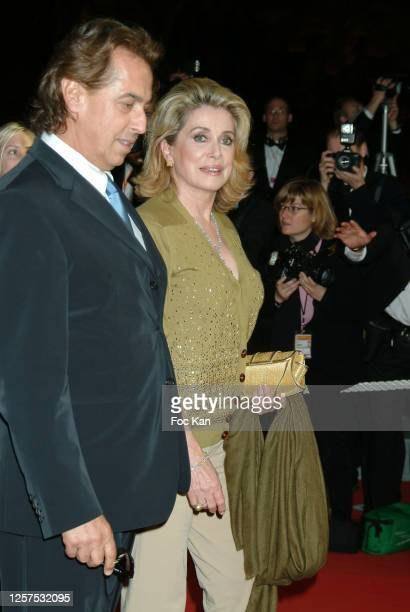 Gilles Dufour and Catherine Deneuve attend the 57th Cannes Film Festival on May 2004, in Cannes, France.