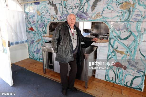 Gilles Esmiol poses in front of a fresco painted by French sculptor Jean Marais and listed as a historical monument in his restaurant 'Nounou' one of...