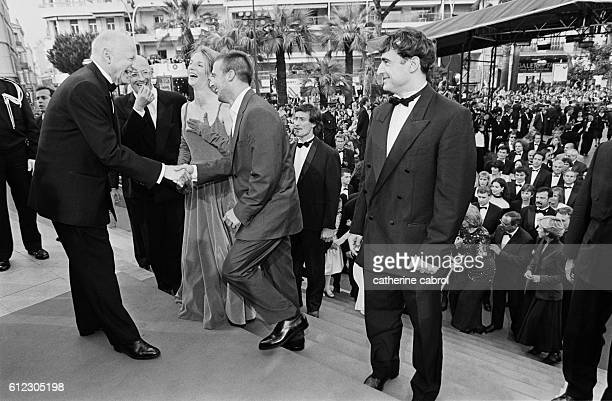 Gilles Jacob stands at the entry of the Palais des Festivals to greet Jacques Audiard Sandrine Kiberlain Mathieu Kassovitz and Albert Dupontel...