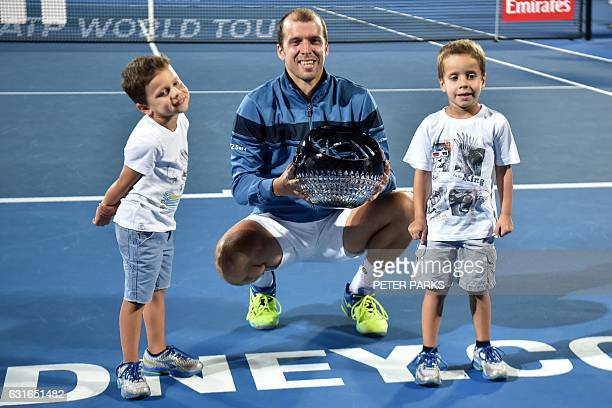 Gilles Muller of Luxembourg holds his trophy with his two sons Lenny and Nils after beating Daniel Evans of Britain in the men's singles final match...