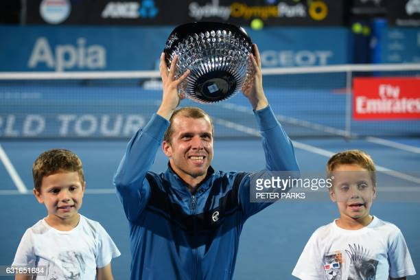 Gilles Muller of Luxembourg holds up his trophy with his sons Lenny and Nils after beating Daniel Evans of Britain in the men's singles final match...