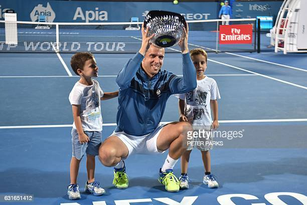 Gilles Muller of Luxembourg holds up his trophy with his two sons Lenny and Nils after beating Daniel Evans of Britain in the men's singles final...