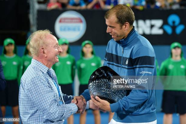 Gilles Muller of Luxembourg receives his trophy from Australian tennis legend Rod Laver after beating Daniel Evans of Britain in the men's singles...
