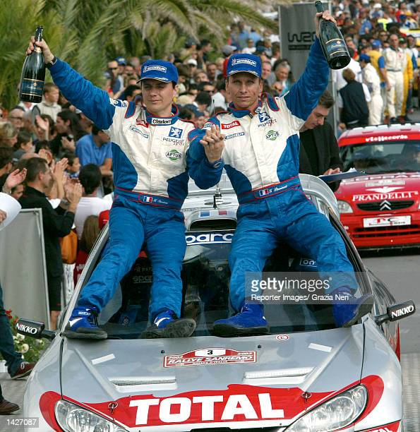 SAN REMO ITALY Gilles Panizzi and his codriver Herve Panizzi of France and the Peugeot 206 WRC team celebrate on the podium following the San Remo...