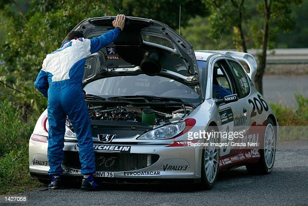 SAN REMO ITALY Gilles Panizzi of France and the Peugeot 206 WRC team checks his engine during the second leg of the San Remo Rally the eleventh stage...