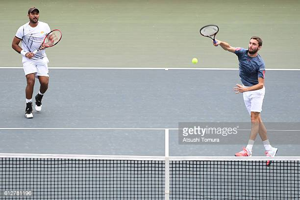 Gilles Simon of France and AisamUlHaq Qureshi of Pakistan in action during the men's doubles first round match against Oliver Marach of Austria and...