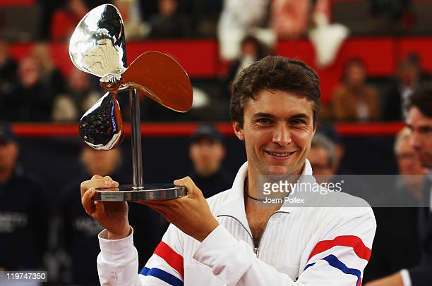 Gilles Simon of France celebrates with the cup after winning his final match against Nicolas Almagro of Spain during the betathome German Open Tennis...