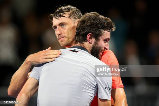 Gilles Simon of France embraces John Millman of Australia during day five of the 2019 Sydney International at the Sydney Olympic Tennis Centre on...