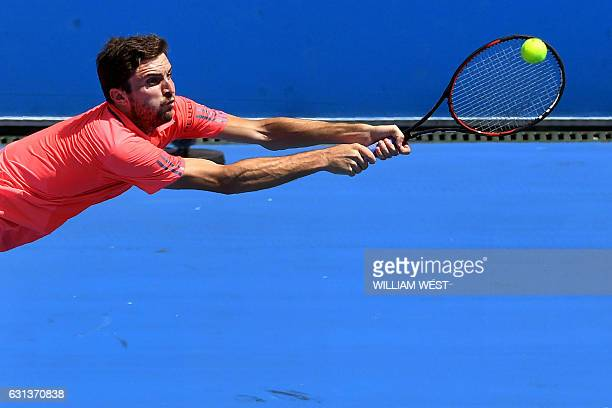 Gilles Simon of France hits a backhand return against Ivo Karlovic of Croatia on the first day of the Kooyong Classic tennis tournament in Melbourne...