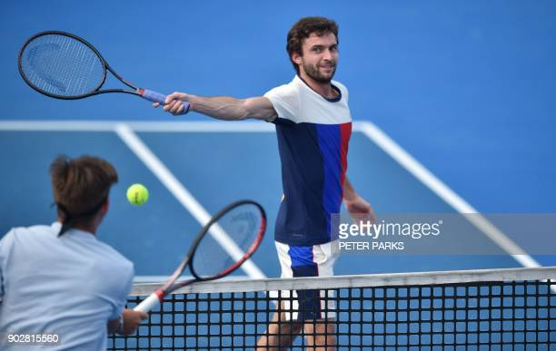 Gilles Simon of France hits a return at Jared Donaldson of the US in their men's singles first round match at the Sydney International tennis...