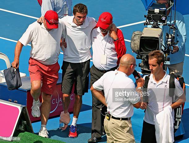 Gilles Simon of France leaves the court injured after his match against Richard Gasquet of France during day three of the AAMI Classic at Kooyong on...