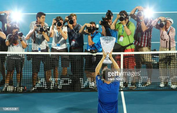 Gilles Simon of France poses for photos after winning the Mens singles final against Viktor Troicki of Serbia during day seven of the 2011 Medibank...