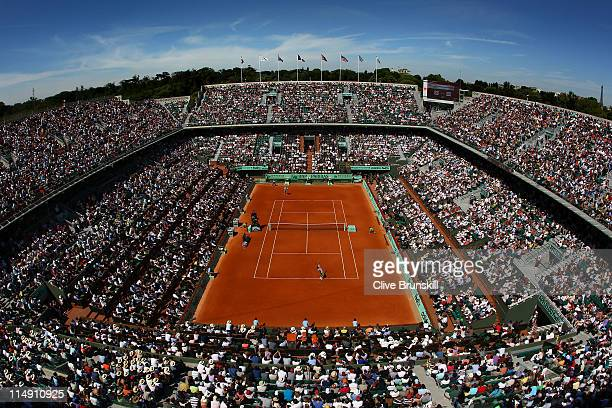 Gilles Simon of France serves in front of a packed Court Philippe Chatrier during the men's singles round three match between Mardy Fish of USA and...