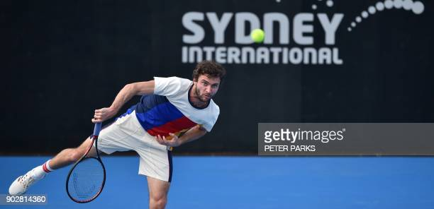 Gilles Simon of France serves to Jared Donaldson of the US in their men's singles first round match at the Sydney International tennis tournament in...