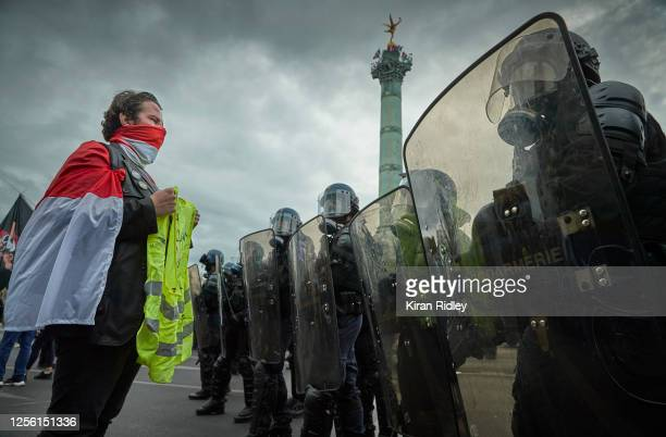 Gillet Jaune or yellow vest protestor stands in front of French riot police in protest during Bastille Day antigovernment demonstrations at Place de...