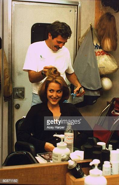 Gillian Anderson costar of cult TV series The XFiles getting hair done by unident stylist on the set of the show