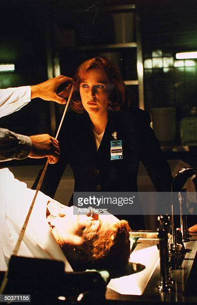 Gillian Anderson costar on cult TV series The XFiles standing near unident extra on the set of the show