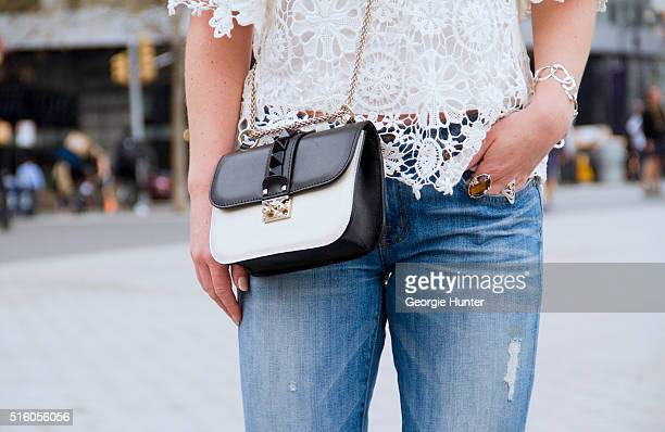 Gillian Del Zotto wearing ripped J Brand Jeans white lace Nightcap Clothing top and black and white Valentino bag with studded detail and gold chain...